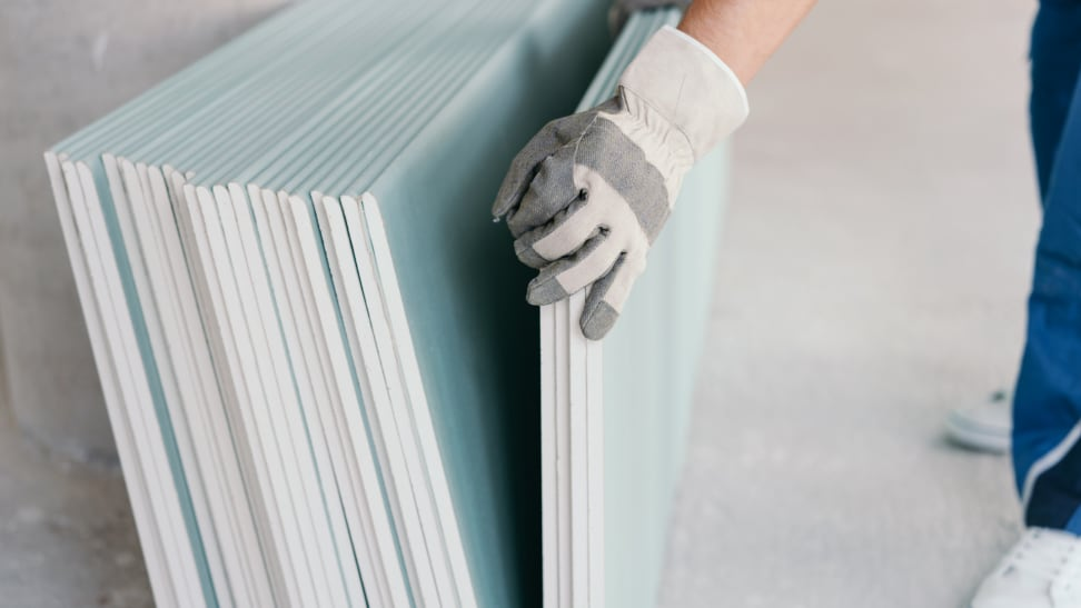 a person lifts a piece of drywall away from a stack