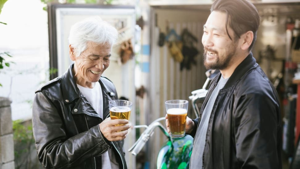 Father and son enjoy a beer outdoors.