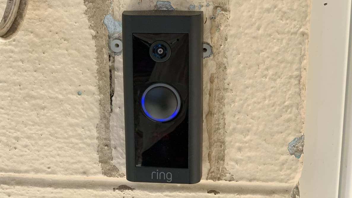 The Ring Video Doorbell Wired hangs on the front of a home.