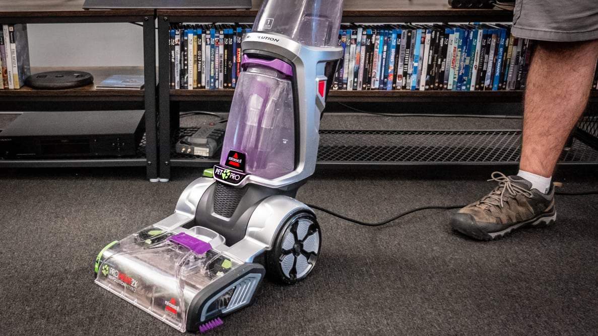 A vacuum stands in a room on a carpet