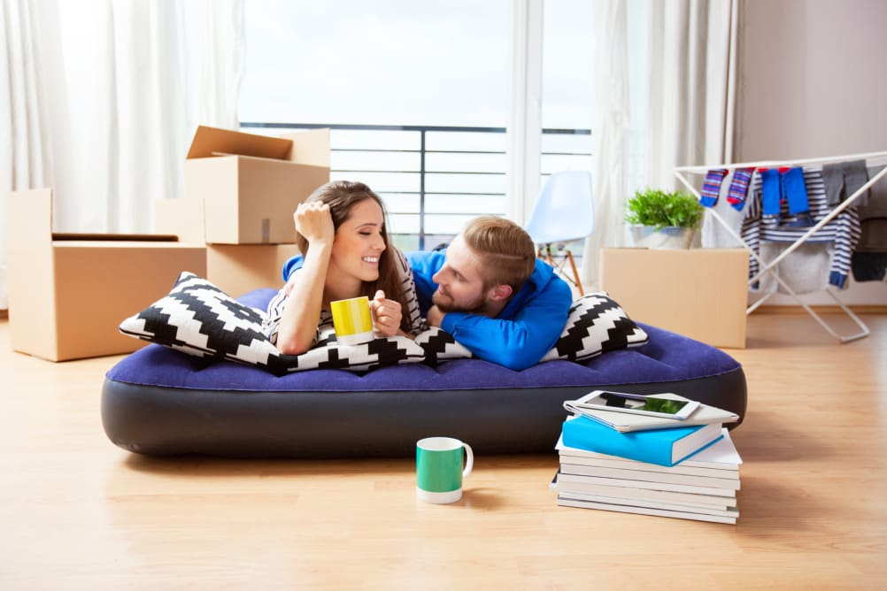 couple on an air mattress after moving