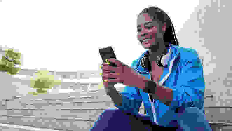 A person in running gear sitting on steps outside and looking at their phone.