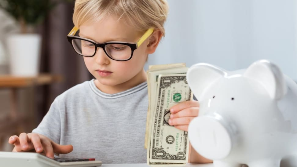 Boy with glasses counting dollar bills with adding machine.
