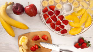 A photo of whole apples and bananas arranged next to a platter of sliced bananas, apples, peaches, and strawberries.
