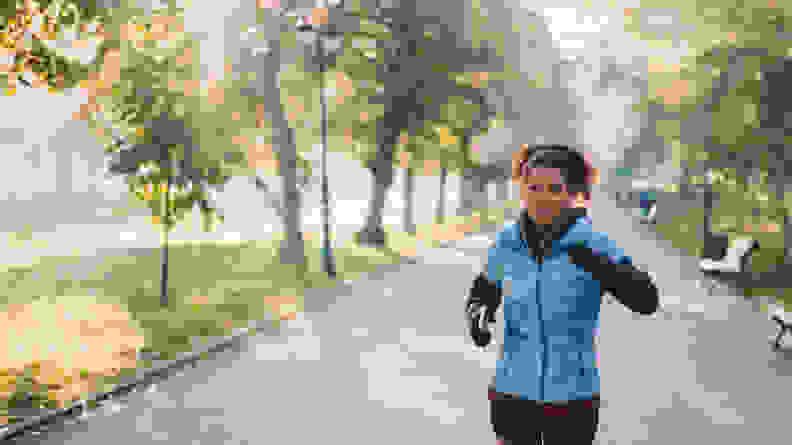 A woman jogging through a park.