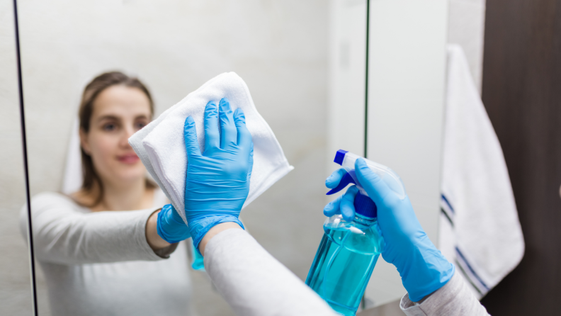Woman using rubber gloves and a microfiber cloth to wipe off mirror.