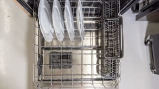 The lower rack of a dishwasher is filled with four white plates