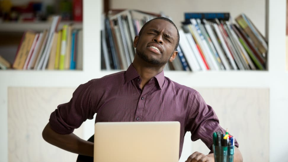 Man touching back in pain while working at his desk with a laptop