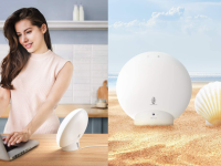 On left, woman smiling while using laptop computer and light therapy lamp. On right, light therapy lamp next to clam on beach for size comparison.