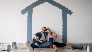 A couple sit inside a room underneath a painted house on a wall.