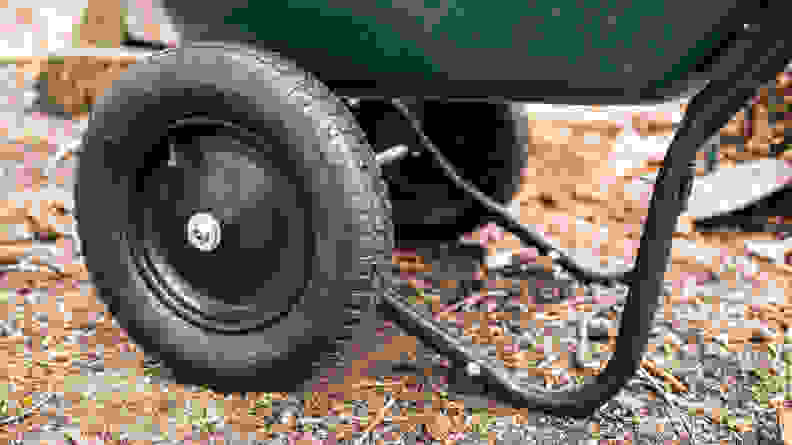 A close-up of the wheels and stabilizing legs of of a wheelbarrow.