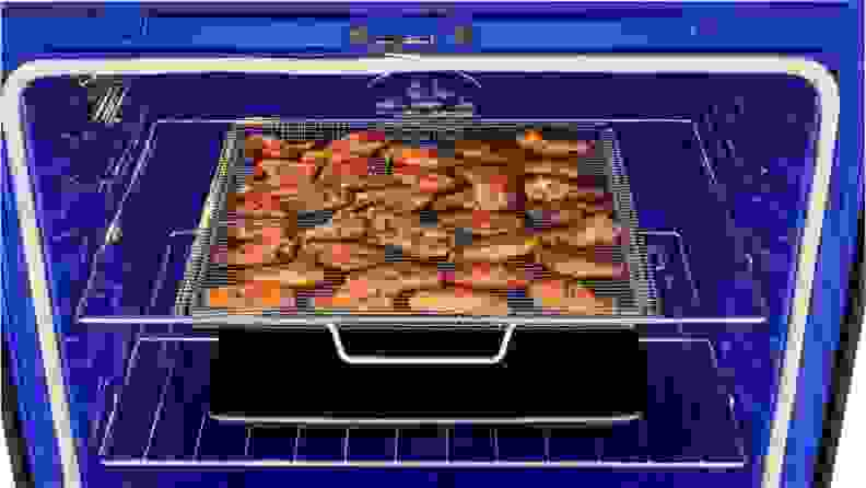 The royal blue inside of an electric oven, displaying a baking sheet filled with cooked chicken wings.