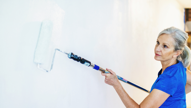 Senior woman wears her hair back in a ponytail as she uses a extended roller brush to paint wall.