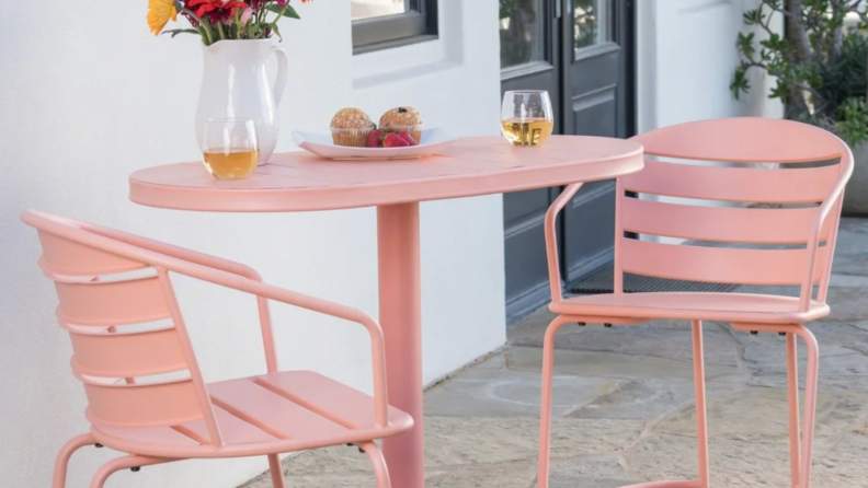 A pink bistro table and chairs sit on a patio.