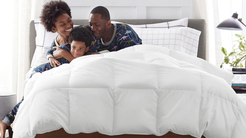 A Black mom, dad, and child hugging in a bed covered by a white down comforter.