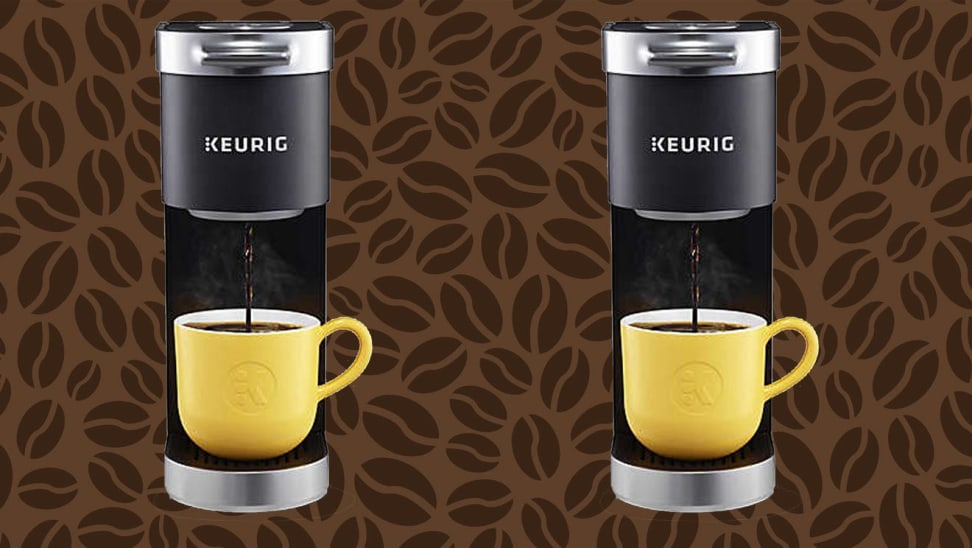 Two black Keurig coffee makers brewing coffee into yellow mugs in front of brown coffee bean background.