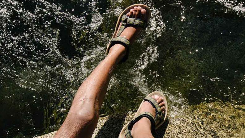 Man wearing Tevas hanging over the water.