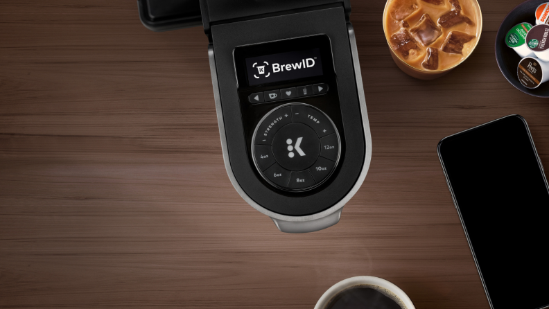 On a brown wooden table, there's a Keurig K-Supreme Plus Smart  pod coffee maker with BrewID technology and a glass of iced coffee next to it.