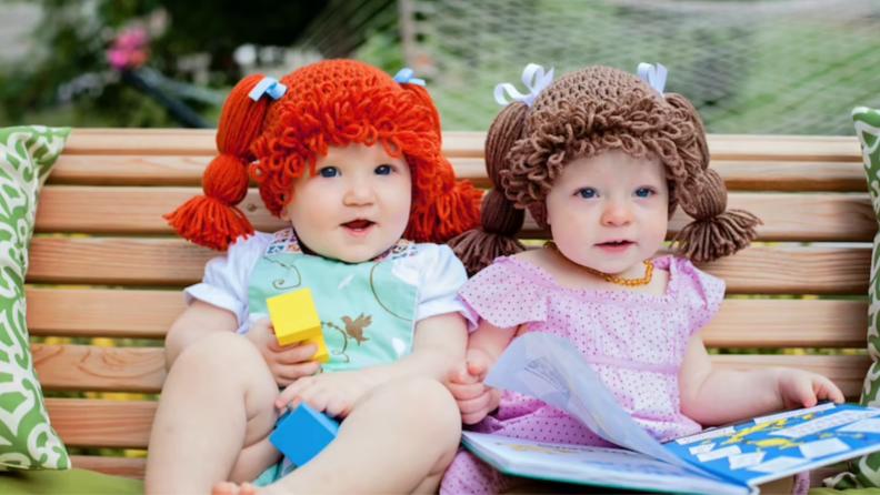 Infants wearing yarn wigs outdoors.