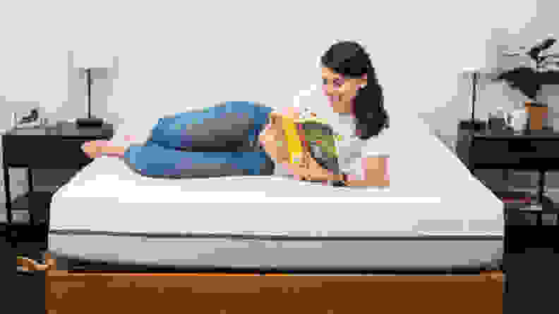 A woman reading a book, laying across a Purple mattress.