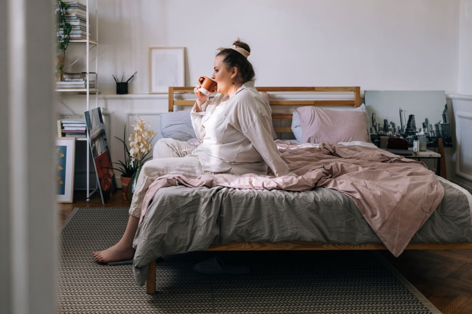 Plus-size woman sitting on edge of bed drinking coffee wearing PJs
