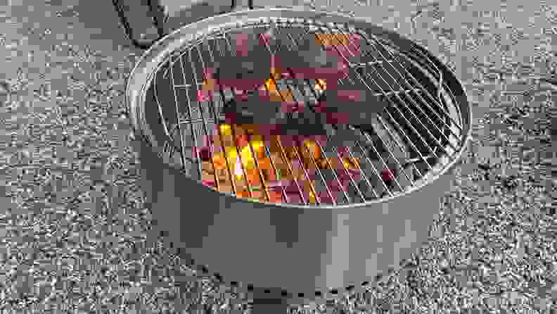 Burger patties cook on a grate over a charcoal grill.