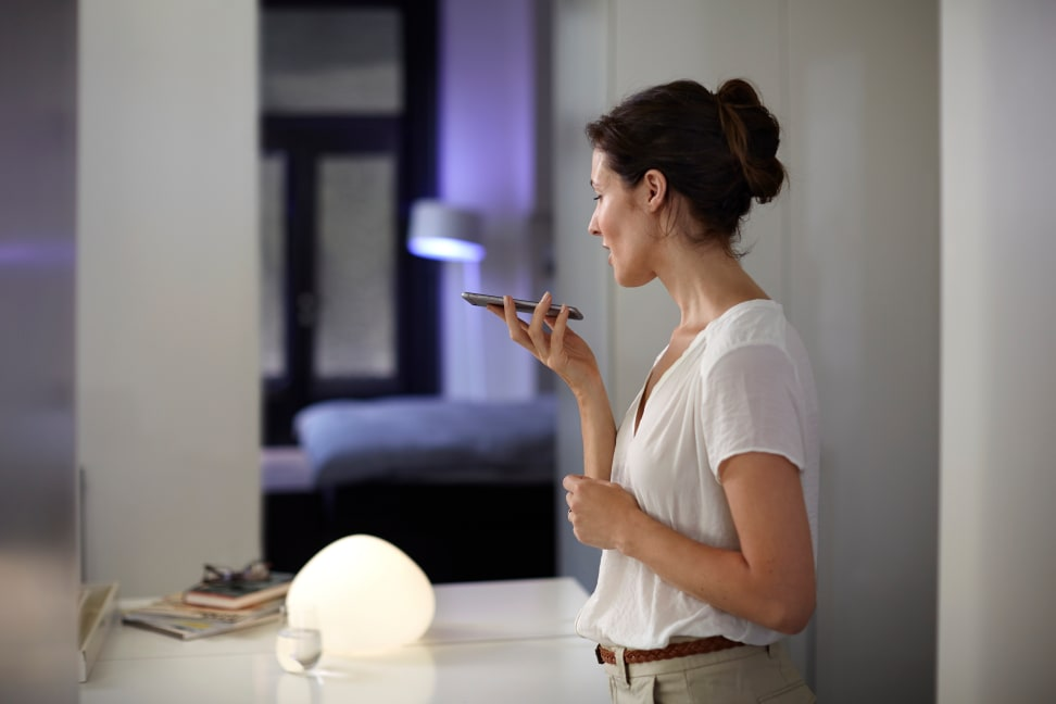 A woman uses Siri to control her Philips Hue lights