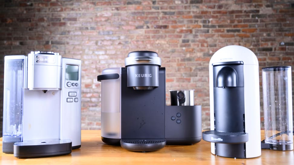 Shown sitting on a table from left to right: The Cuisinart SS-10, Keurig K-Cafe, and Nespresso VertuoPlus by Breville single-serve coffee makers.