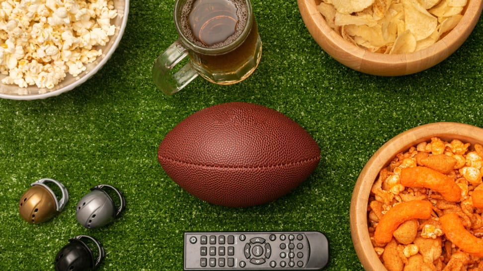 Super Bowl party snacks, a TV remote, and a football