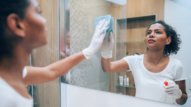 Woman wearing clear gloves and using spray bottle and cloth to wipe off mirror.