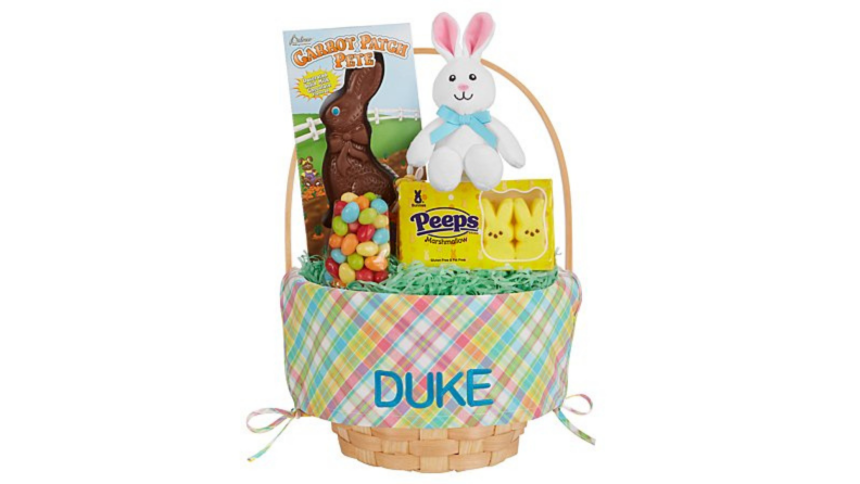 A gingham Easter basket with a child's name embroidered on it with a big chocolate bunny and other sweets.