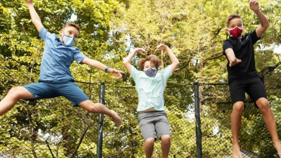 Three kids jump on a trampoline while wearing face masks.