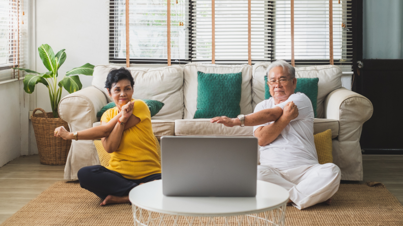 an older couple practices arm stretching while sitting on the floor