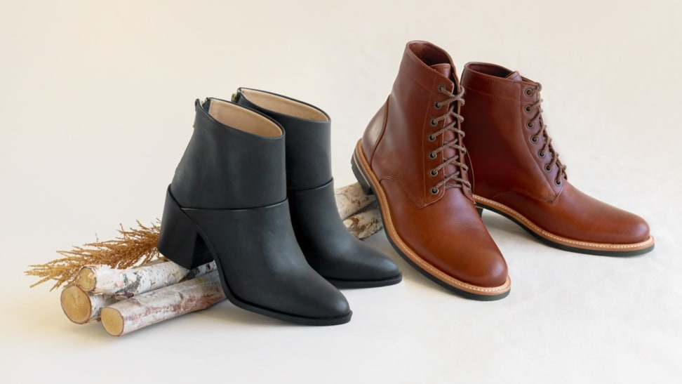 A black pair of boots next to a brown pair of boots on a stick.