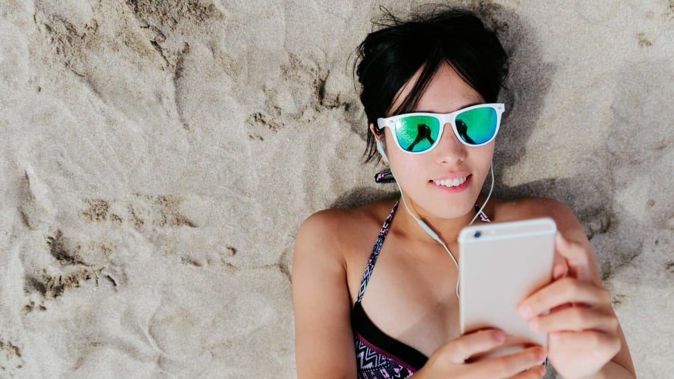 A person at the beach using their smartphone