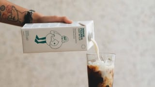 A tattooed person pour oat milk from a carton into a glass of iced coffee.