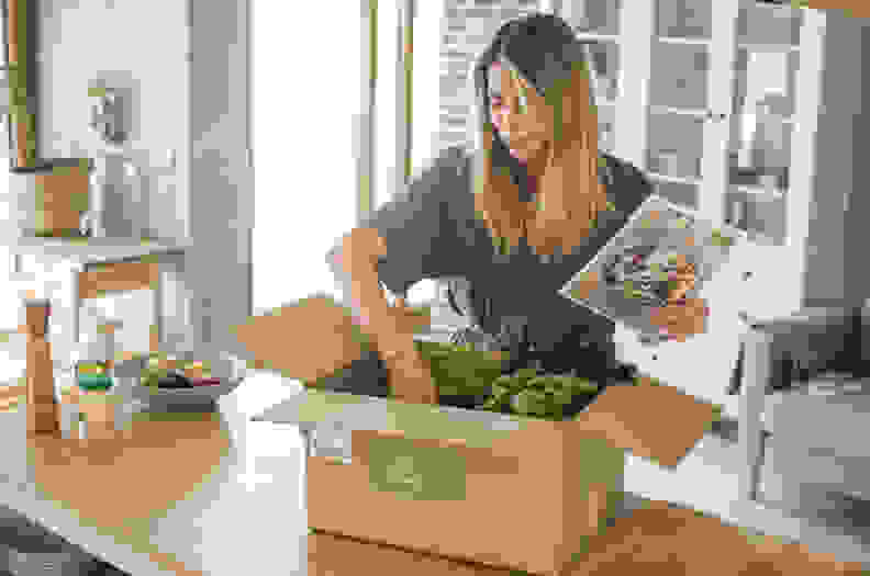 Woman is received box loaded with organic vegetables from delivery service. She is up to make some fantastic vegan meal