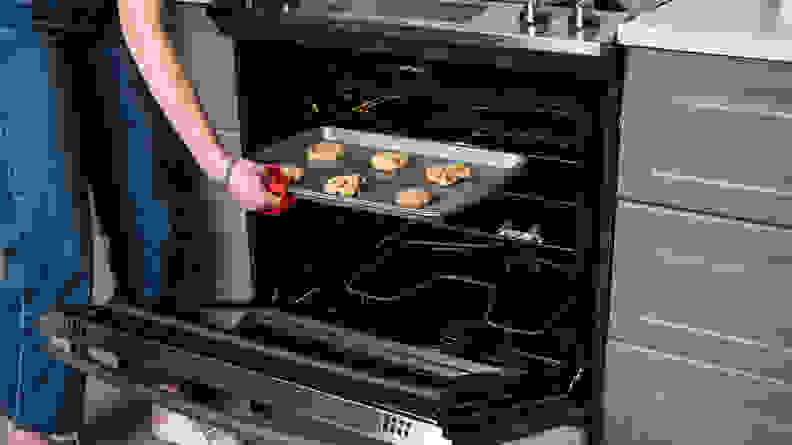 A person removes a tray of cookies from the oven using a red oven mitt.
