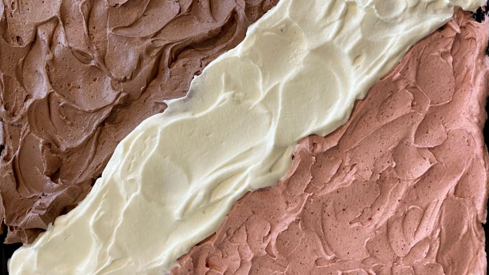 A photo of Neapolitan icing on a sheet cake in the following order from left to right: chocolate, vanilla, and strawberry.