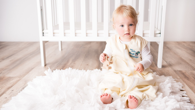 A baby wearing a cream onesie sits in front of a crib.