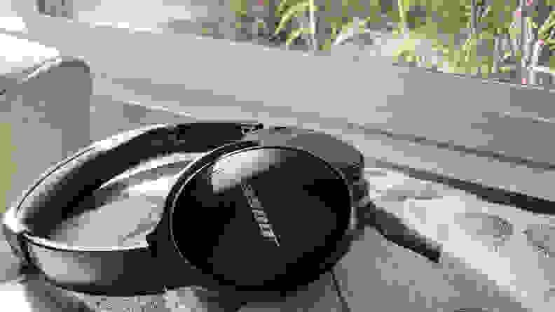 The Bose QC45 headphones sitting atop a pillow in front of a window