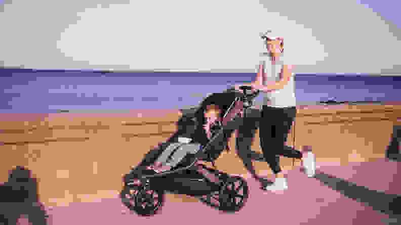A woman jogging along a sea wall pushing a child in a jogging stroller.
