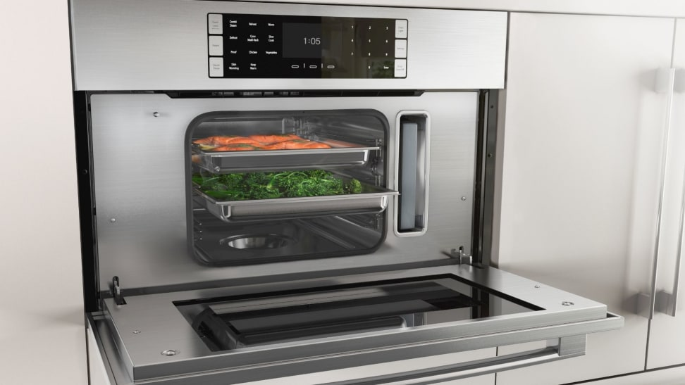A wall oven with its door open revealing steamed foods.