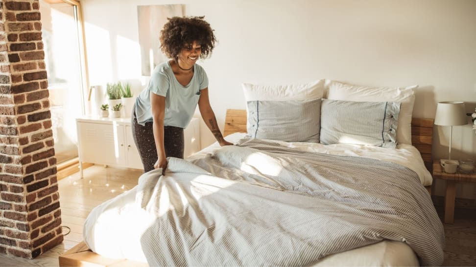 A person positions a duvet cover over a mattress in a bedroom