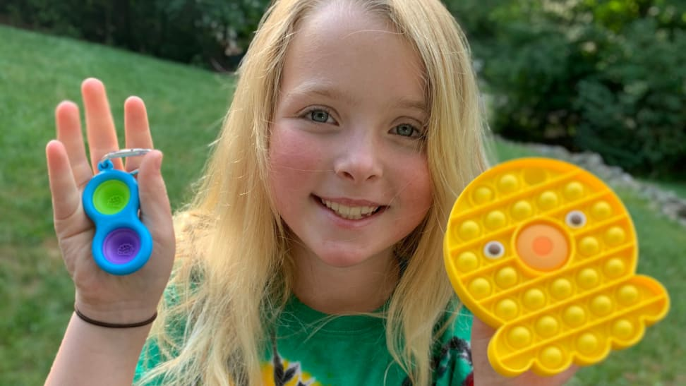 a little girl hold's up two pop-it fidget toys, one small 2-button one and another larger squid-shaped one