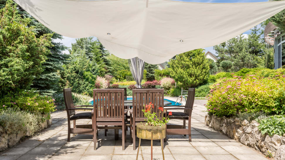 patio with table is covered by a shade sail