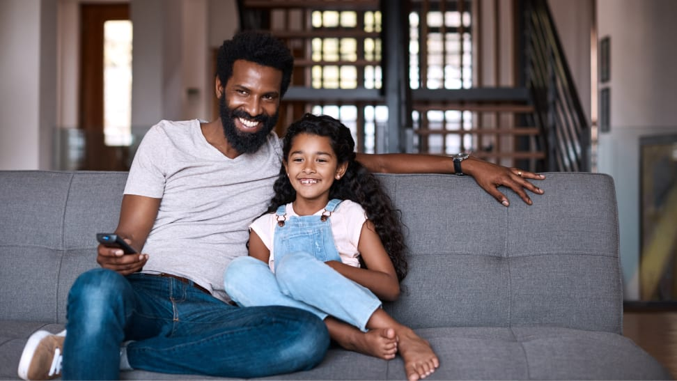 A man and a young girl on a gray couch together watching TV