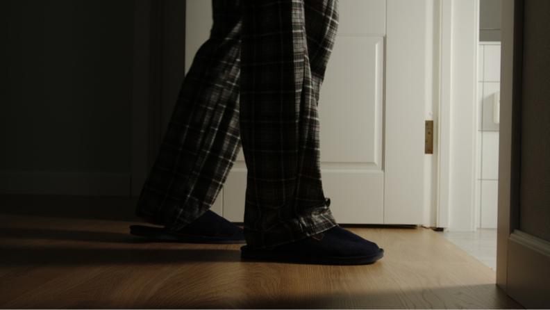 Man wearing pajama pants walking across hard wood floor.