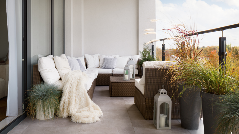 A white couch sits on a balcony surrounded by plants.