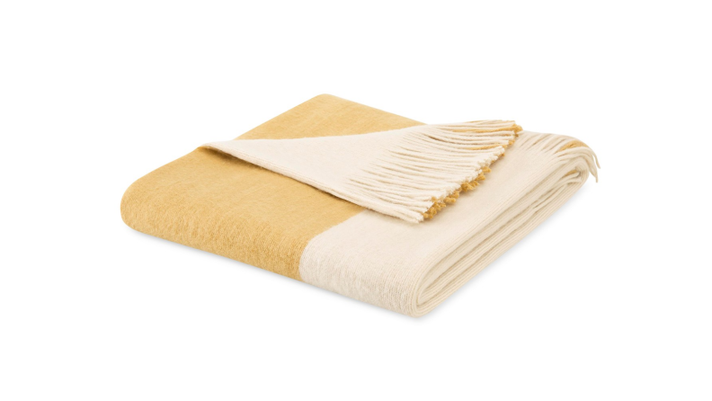 An image of a colorblocked white and gold blanket folded.